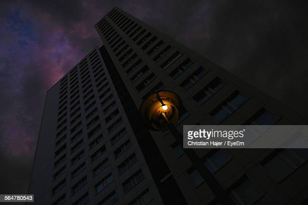 Low Angle View Of Illuminated Street Light Against Dark Building At Night