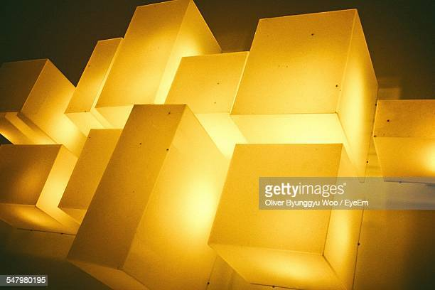 Low Angle View Of Illuminated Yellow Cube Shape Lamps