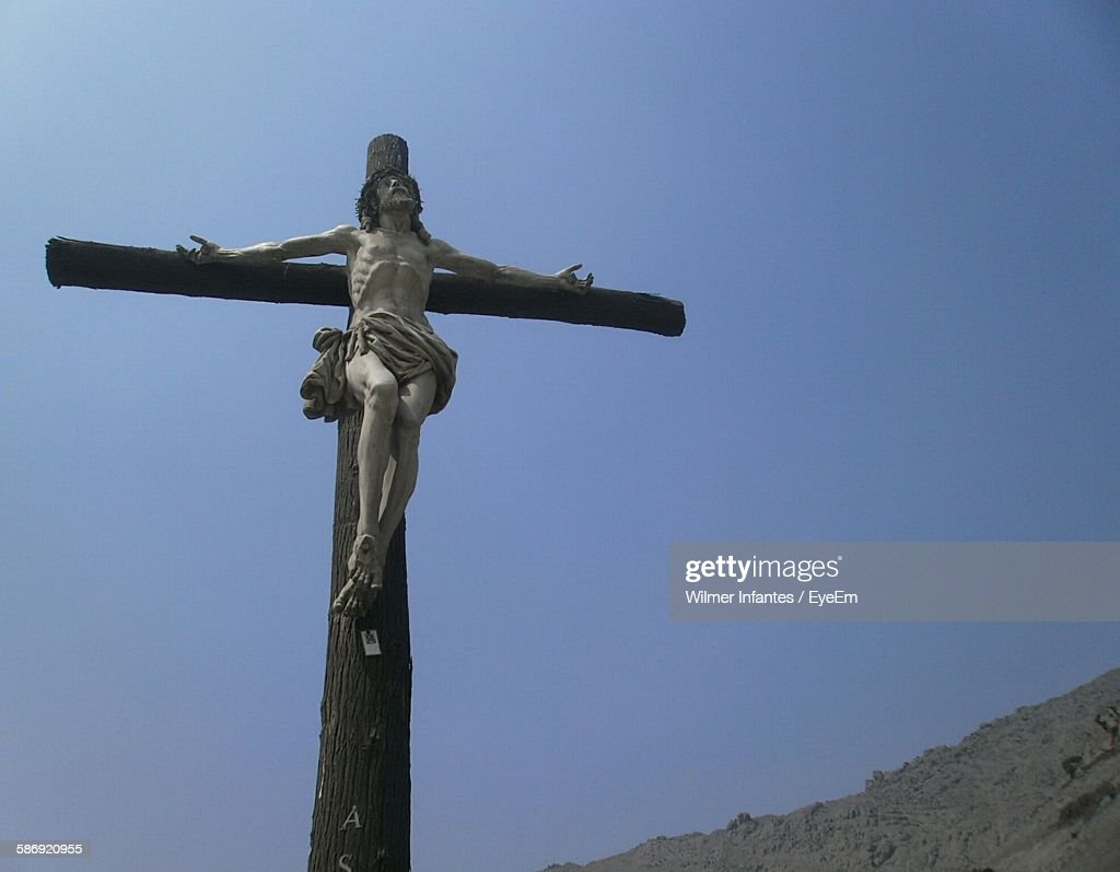 low angle view of jesus christ sculpture on cross against clear