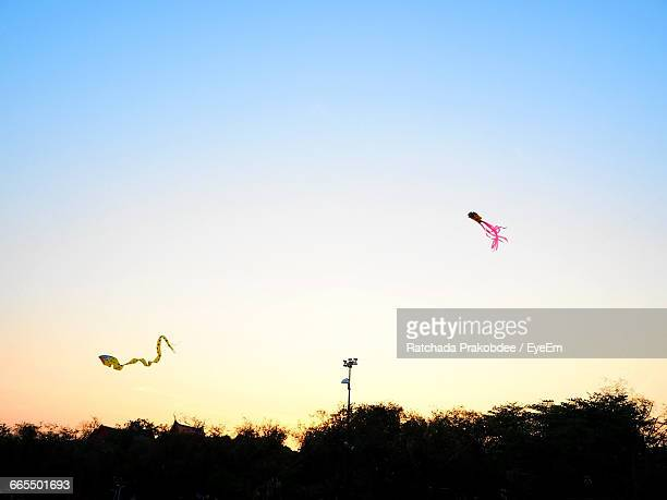 Low Angle View Of Kites Flying Against Clear Sky During Sunset