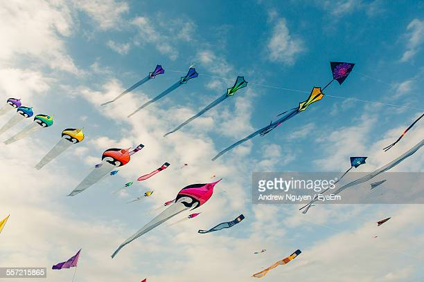 Low Angle View Of Kites Flying In Cloudy Sky