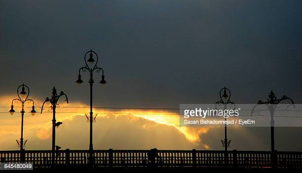 Low Angle View Of Lamp Posts Against Clouds