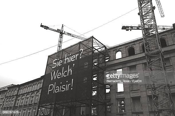 Low Angle View Of Large Advertisement Billboard On Building With Scaffoldings And Cranes