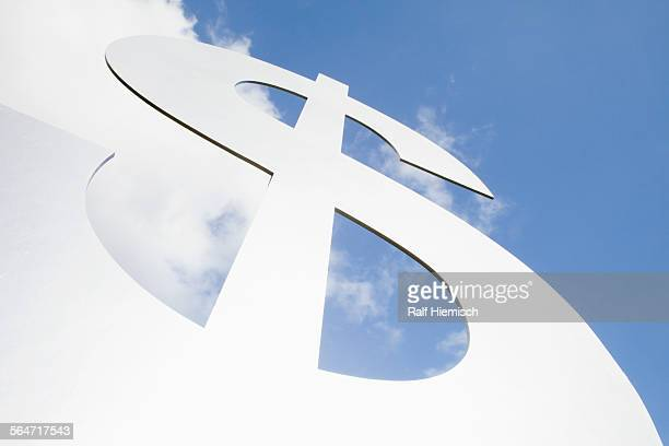 Low angle view of large dollar sign against sky