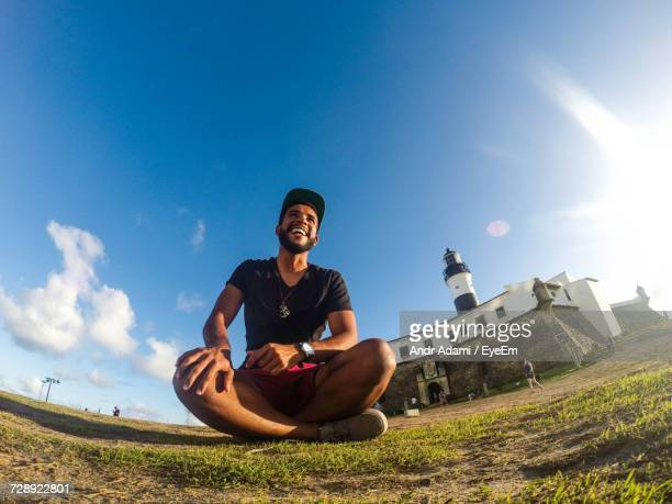 Low Angle View Of Laughing Young Man Sitting On Grassy Field Against Sky On Sunny Day