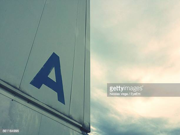 Low Angle View Of Letter A On Metallic Wall Against Cloudy Sky