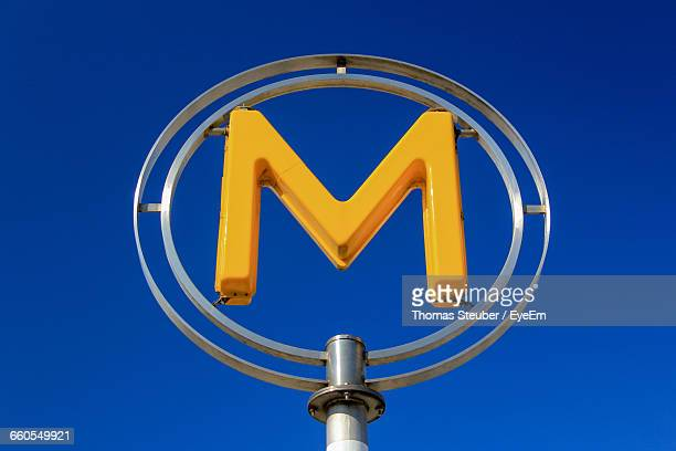 Low Angle View Of Letter M Symbol Against Clear Blue Sky
