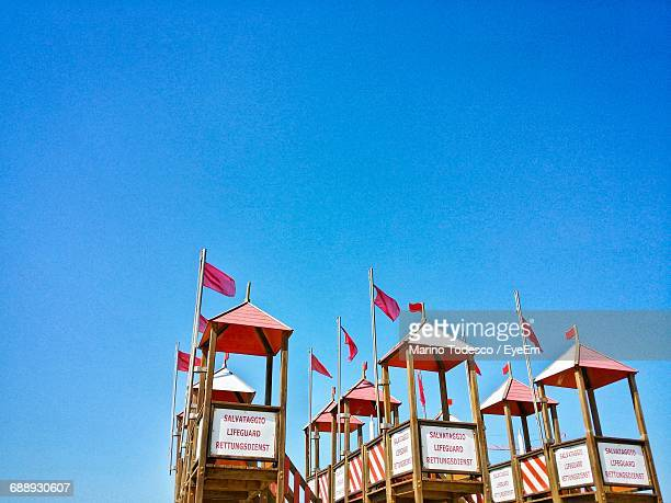Low Angle View Of Lifeguard Towers Against Clear Blue Sky