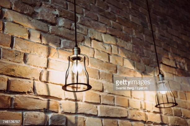 Low Angle View Of Light Bulbs Hanging Against Brick Wall