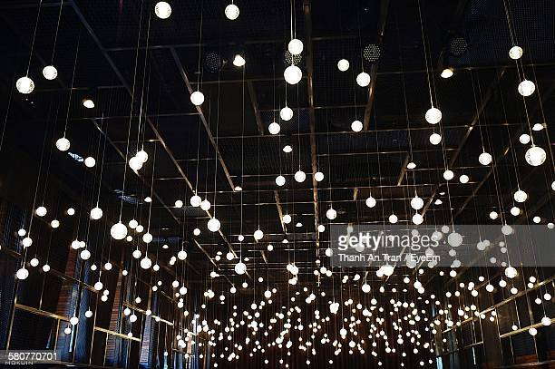 Low Angle View Of Light Bulbs Hanging At Restaurant
