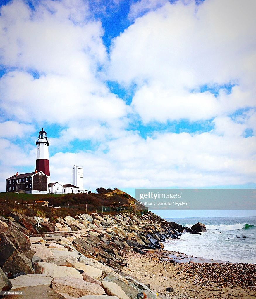 Low Angle View Of Lighthouse By Sea Against Cloudy Sky At Montauk Point State Park