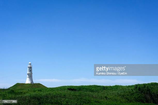 Low Angle View Of Lighthouse On Field Against Clear Blue Sky