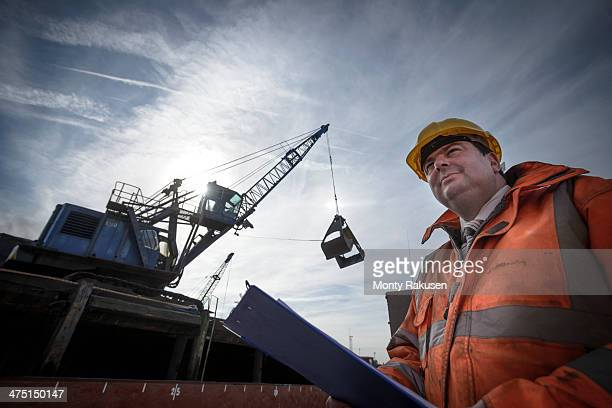 Low angle view of load master checking ship loading