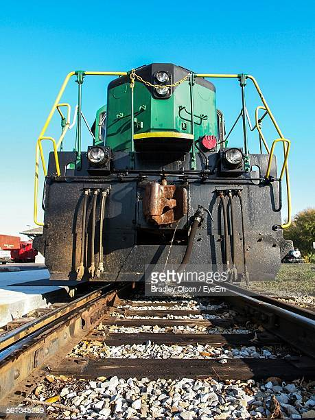 Low Angle View Of Locomotive On Railroad Tracks Against Clear Blue Sky