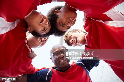 Low Angle View Of Male High School Soccer Players And Coach Having Team Talk : Stock Photo