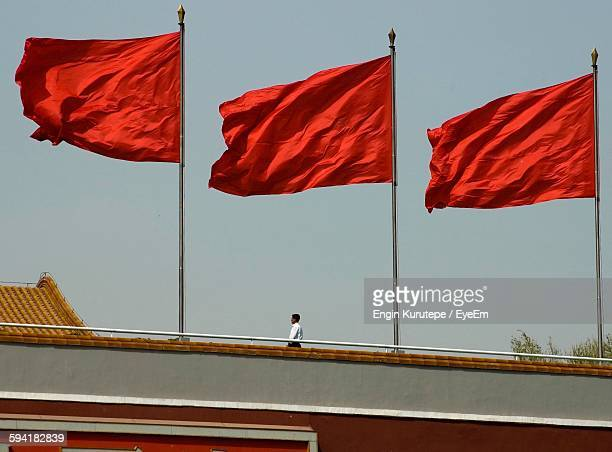 Low Angle View Of Man And Red Flags On Building Against Sky