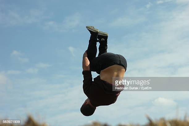 Low Angle View Of Man Backflipping In Mid-Air Against Sky
