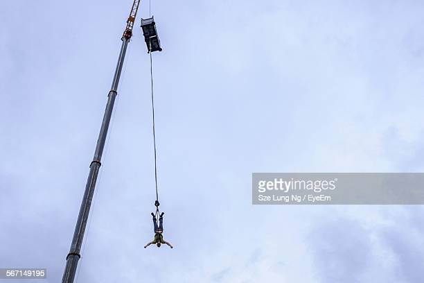 Low Angle View Of Man Bungee Jumping From Crane Against Sky