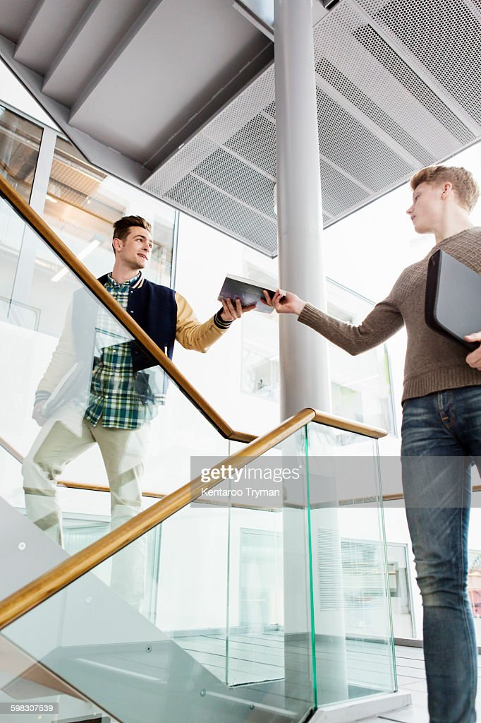 Low angle view of man giving book to friend