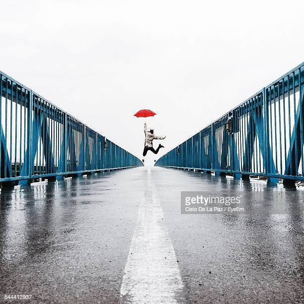 Low Angle View Of Man In Mid-Air With Red Umbrella Over Bridge Against Clear Sky