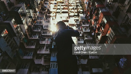 Low Angle View Of Man Photographing Apartment Skyscraper From Mobile Phone