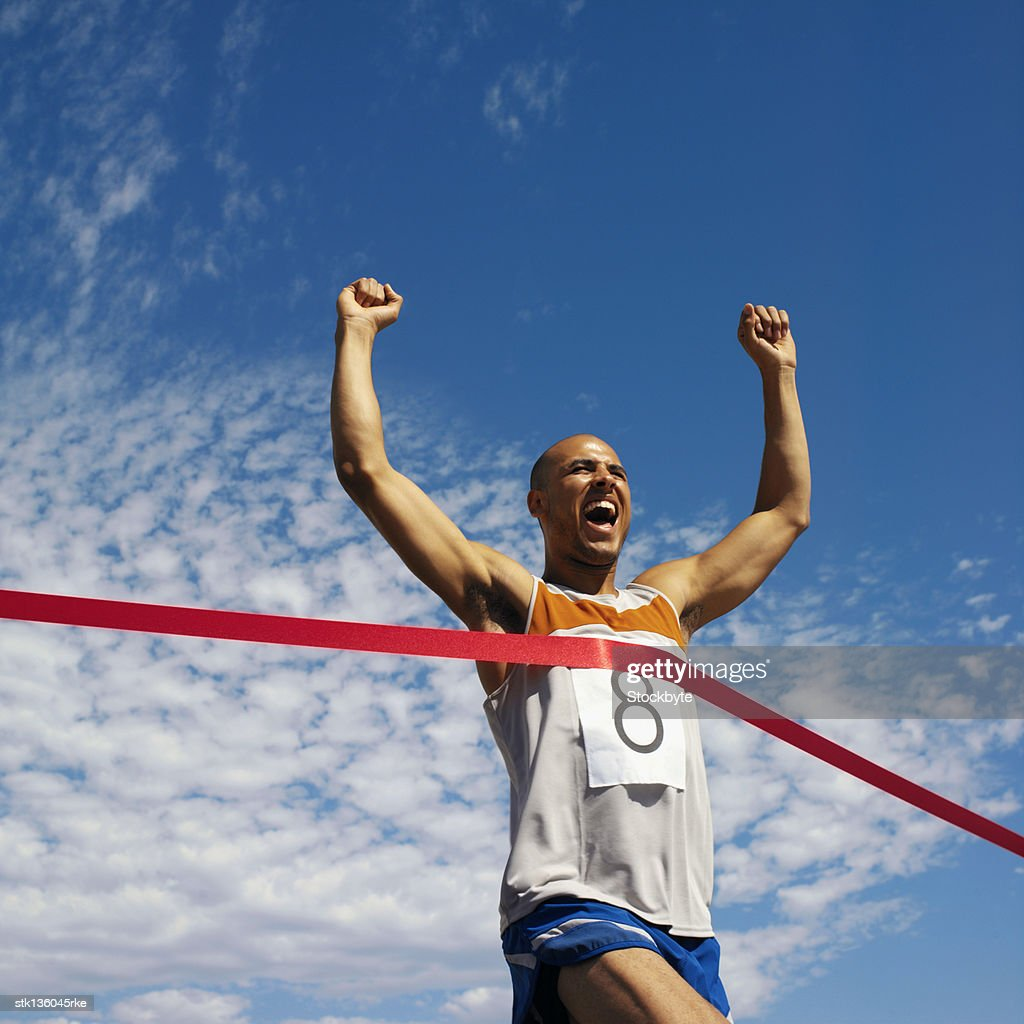low angle view of man running, reaching finish line : Stock Photo