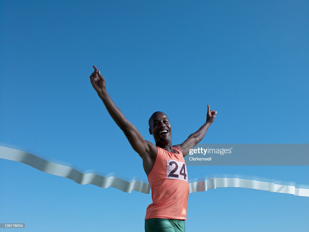 Low angle view of man smiling and crossing finish line : Stock Photo