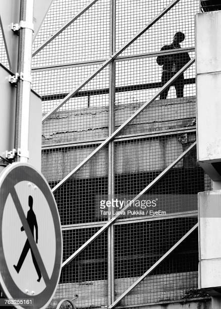 Low Angle View Of Man Standing On Building Seen Through Fence
