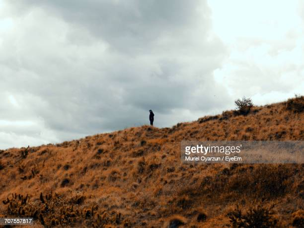 Low Angle View Of Man Standing On Mountain Against Cloudy Sky
