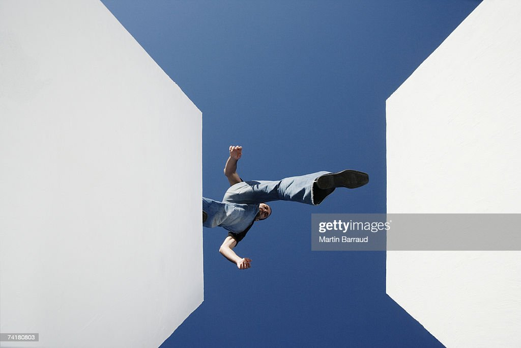 Low angle view of man walking across high gap outdoors