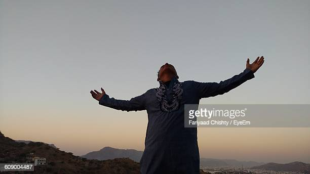 Low Angle View Of Man With Arms Outstretched Against Sky At Sunset