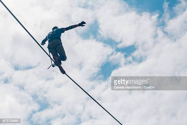 Low Angle View Of Man With Arms Outstretched Walking On Tightrope Against Cloudy Sky