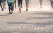 Low angle view of marathon runners running in sunny street, Blurred abstract motion group of runners, city street. Sport background. Fitness and healthy lifestyle, sport activity