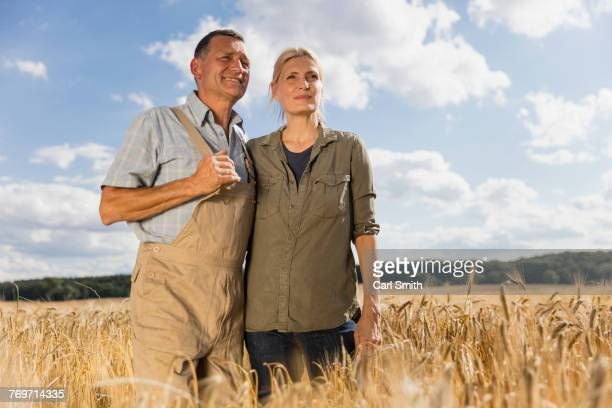Low angle view of mature couple standing amidst crops at farm against sky on sunny day