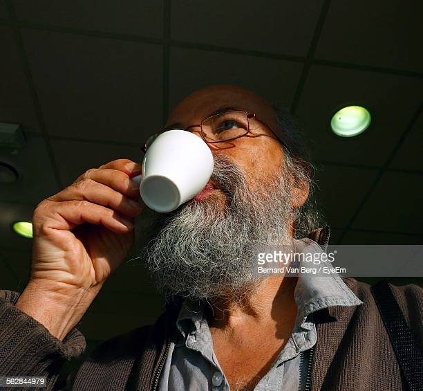 Low Angle View Of Mature Man Drinking Coffee In Restaurant