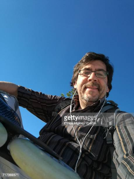 Low Angle View Of Mature Skater Listening Music Through Headphones Against Clear Blue Sky
