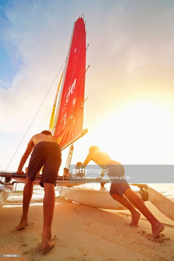 Low angle view of men pushing sailboat into ocean from beach