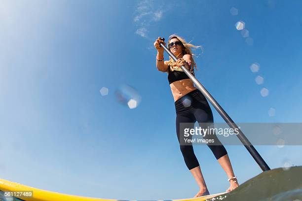 Low angle view of mid adult woman standup paddleboarding