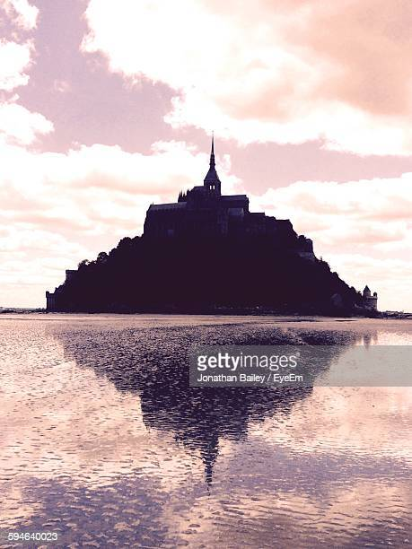 Low Angle View Of Mont Saint-Michel At Sea Against Sky During Sunset