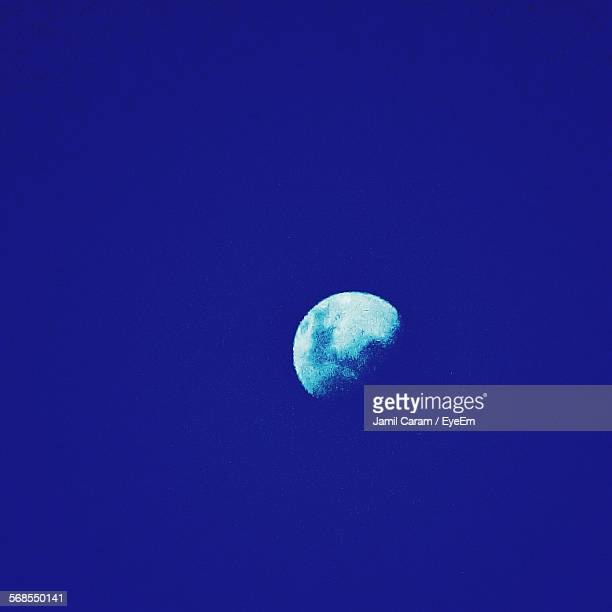 Low Angle View Of Moon In Blue Sky At Dusk