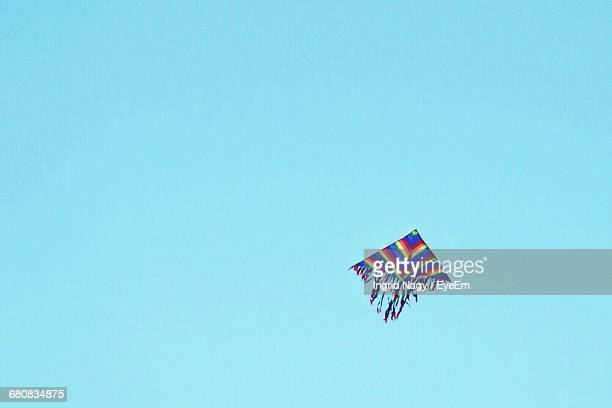 Low Angle View Of Multi Colored Kite Flying Against Clear Blue Sky