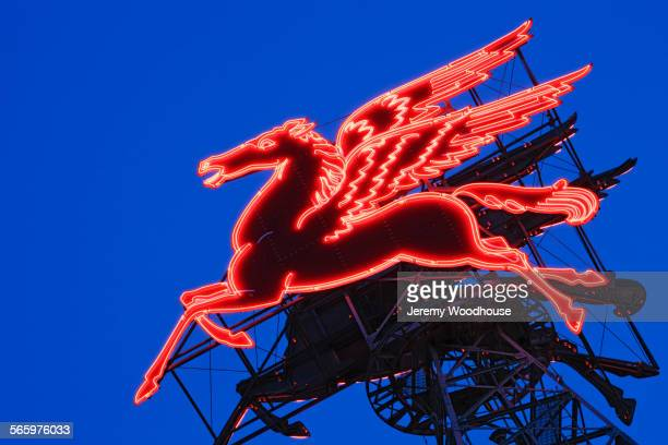 Low angle view of neon pegasus sign under dusk sky