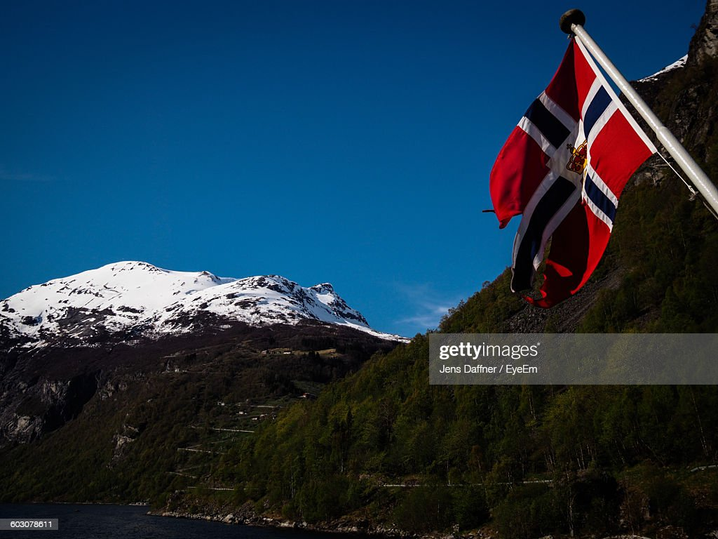 low angle view of norwegian flag and snowcapped mountains against
