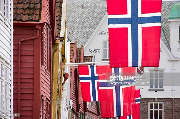 Low Angle View Of Norwegian Flags Hanging By Building