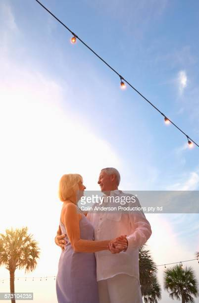 Low angle view of older Caucasian couple dancing outdoors
