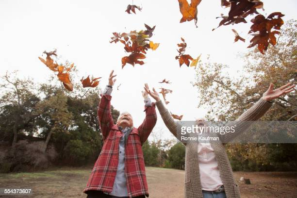 Low angle view of older couple playing in autumn leaves