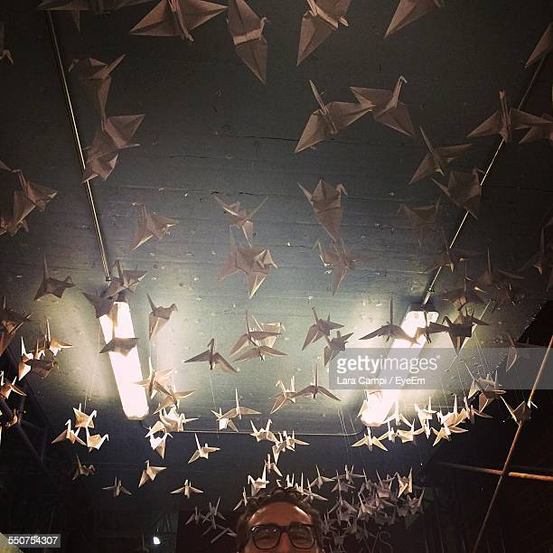 Low Angle View Of Origami Hanging Against Ceiling Over Man