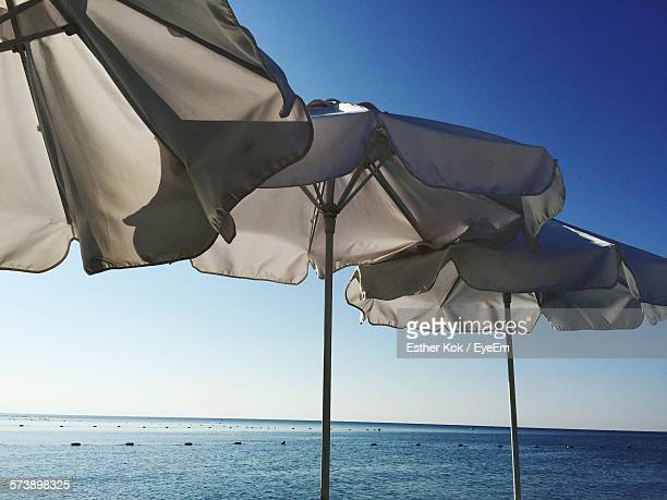 Low Angle View Of Parasols On Beach Against Clear Blue Sky