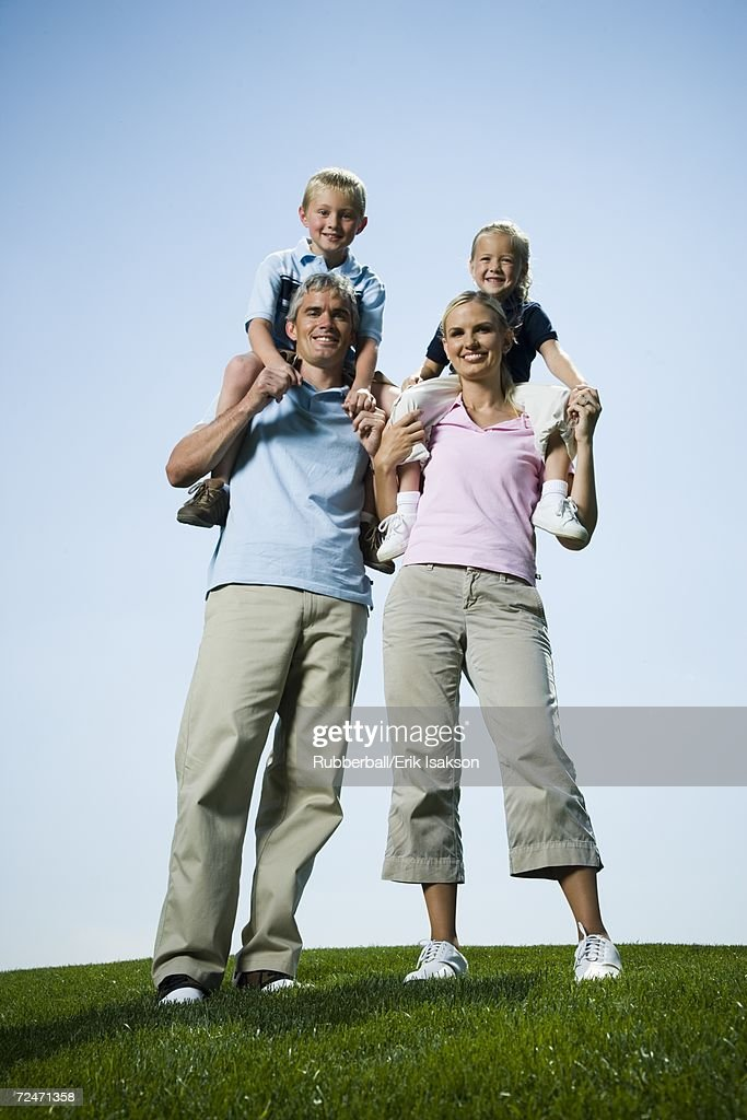 Low angle view of parents carrying their two children on their shoulders : Stock Photo