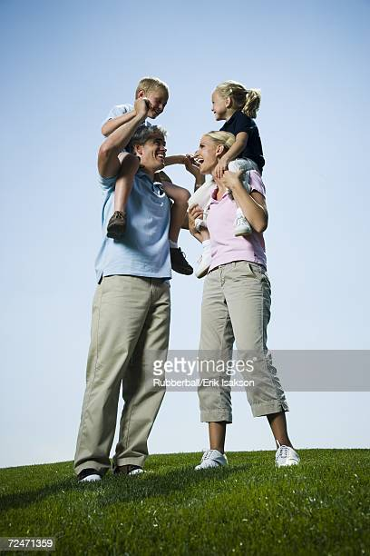 Low angle view of parents carrying their two children on their shoulders